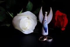 , Άσπρων και κόκκινων τριαντάφυλλα γαμήλιων δαχτυλιδιών, αριθμού αγγέλου στο μαύρο υπόβαθρο Συμβολική έννοια — αγάπη, πίστη, γάμο στοκ φωτογραφία με δικαίωμα ελεύθερης χρήσης