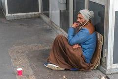 Άστεγη συνεδρίαση ατόμων στην οδό στοκ φωτογραφία