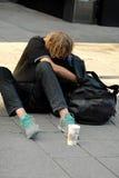 Άστεγη συνεδρίαση ατόμων σε μια οδό Στοκ Εικόνες