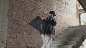 Άστεγοι επάνω στα σκαλοπάτια με την τσάντα απορριμάτων πίσω από την πλάτη του φιλμ μικρού μήκους