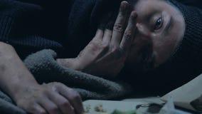 Άστεγοι που τρώνε το ψωμί, που βρίσκεται στο κρύο πεζοδρόμιο, την πείνα και την ένδεια στον αδικημένο πληθυσμό απόθεμα βίντεο