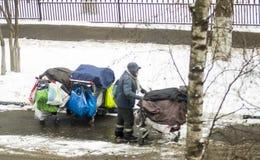 Άστεγο άτομο με τη γενειάδα που ωθεί ένα κάρρο αγορών με όλες τις κατοχές του Στοκ Φωτογραφία