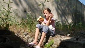 Άστεγο λυπημένο παιδί στο εγκαταλειμμένο δυστυχισμένο περιπλανώμενο κορίτσι σπιτιών που τρώει το λουκάνικο 4K ψωμιού απόθεμα βίντεο