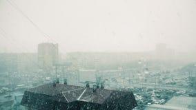 Άσχημος καιρός στη σύγχρονη πόλη και βαριά άποψη χιονοπτώσεων από το παράθυρο απόθεμα βίντεο