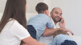 Άτακτα μικρά παιδιά που δεν αφήνουν τον μπαμπά τους να μιλήσει στο τηλέφωνο Στοκ Εικόνα