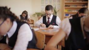 Άτακτος μαθητής στη σχολική στολή που κατασκευάζει ένα αεροπλάνο εγγράφου κατά τη διάρκεια του μαθήματος απόθεμα βίντεο