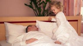Άτακτο κορίτσι μικρών παιδιών ξυπνήστε και τρέξιμο μακρυά από το κρεβάτι πατέρων φιλμ μικρού μήκους