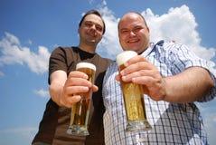 άτομα δύο εκμετάλλευσης μπύρας Στοκ φωτογραφία με δικαίωμα ελεύθερης χρήσης