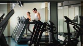 Άτομα και ένα κορίτσι που τρέχει treadmill στη γυμναστική απόθεμα βίντεο