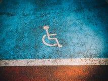 Άτομα με ειδικές ανάγκες που σταθμεύουν το σημάδι invalide που χρωματίζεται στην μπλε άσφαλτο Στοκ φωτογραφίες με δικαίωμα ελεύθερης χρήσης