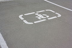 Άτομα με ειδικές ανάγκες που σταθμεύουν το σημάδι στην άσφαλτο τα άτομα με ειδικές ανάγκες υπογράφουν το σημείο χώρων στάθμευσης Στοκ Φωτογραφία