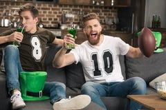 Άτομα με τα γυαλιά μπύρας που προσέχουν το ποδόσφαιρο Στοκ εικόνα με δικαίωμα ελεύθερης χρήσης