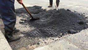 Άτομα με τα φτυάρια που επισκευάζουν το δρόμο απόθεμα βίντεο