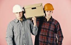 Άτομα με το γκρινιάρικο κουτί από χαρτόνι λαβής προσώπων στο ρόδινο υπόβαθρο Παράδοση, αποθήκη εμπορευμάτων και έννοια συσκευασία Στοκ εικόνες με δικαίωμα ελεύθερης χρήσης