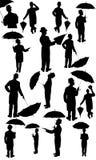 Άτομα με το καπέλο και την ομπρέλα στη σκιαγραφία Στοκ Φωτογραφίες