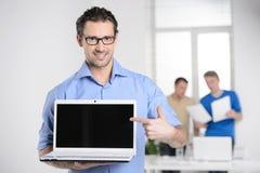 Άτομα με το lap-top. Ευτυχής νέος επιχειρηματίας που κρατά ένα lap-top και po Στοκ εικόνες με δικαίωμα ελεύθερης χρήσης