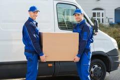 Άτομα παράδοσης που φέρνουν το κουτί από χαρτόνι ενάντια στο φορτηγό Στοκ Εικόνα