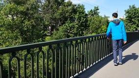 Άτομα περιπάτων ανάπηρα στην πόλη Πλησιάζει το φράκτη της γέφυρας και θαυμάζει την άποψη Χωλότητα, εγκεφαλική παράλυση απόθεμα βίντεο