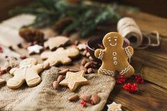 Άτομα πιπεροριζών σε ένα ξύλινο υπόβαθρο τα μπισκότα Χριστουγέννων βρίσκουν ότι οι εικόνες φαίνονται περισσότερο οι ίδιες σειρές  Στοκ Φωτογραφία