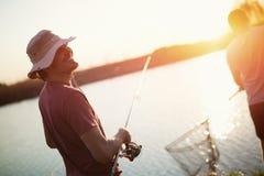 Άτομα που αλιεύουν στο ηλιοβασίλεμα και που χαλαρώνουν απολαμβάνοντας το χόμπι Στοκ φωτογραφία με δικαίωμα ελεύθερης χρήσης