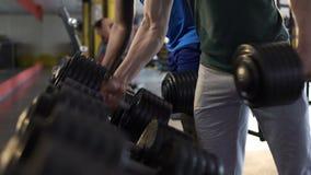 Άτομα που ασκούν με τους βαριούς αλτήρες στη γυμναστική, χτίζοντας ισχυροί μυϊκοί οργανισμοί φιλμ μικρού μήκους