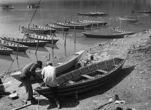 Άτομα που επισκευάζουν τις βάρκες κωπηλασίας μπροστά από τη λίμνη Pokhara Νεπάλ Στοκ Εικόνες