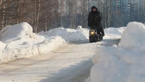 Άτομα που οδηγούν στο μίνι όχημα για το χιόνι αντιολισθητικών αλυσίδων με ένα ρυμουλκό σε έναν χειμερινό δρόμο απόθεμα βίντεο