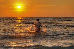 Άτομα που παίζουν το νερό στην παραλία με το ηλιοβασίλεμα Στοκ φωτογραφίες με δικαίωμα ελεύθερης χρήσης