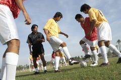 Άτομα που παίζουν το ποδόσφαιρο ενώ διαιτητής που προσέχει τους Στοκ Εικόνα