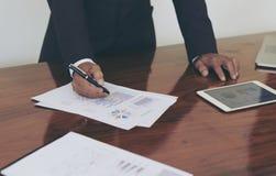 Άτομα που στέκονται στο γραφείο και το λειτουργώντας χέρι εγγράφων γραψίματος κοντά επάνω Στοκ φωτογραφία με δικαίωμα ελεύθερης χρήσης