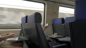 Άτομα που χρησιμοποιούν το κινητό τηλέφωνο και το lap-top στη αμαξοστοιχία περιφερειακού σιδηροδρόμου φιλμ μικρού μήκους