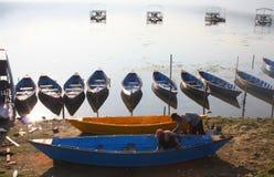 Άτομα που χρωματίζουν τις ζωηρόχρωμες βάρκες κωπηλασίας μπροστά από τη λίμνη Pokhara Νεπάλ Στοκ Φωτογραφίες