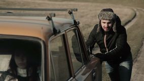 Άτομα που ωθούν το αναλύω αυτοκίνητο στο χειμώνα Συνεδρίαση γυναικών στη ρόδα φιλμ μικρού μήκους