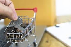 Άτομα ` s που μαζεύουν με το χέρι τα νομίσματα σε ένα καροτσάκι σε ένα πληκτρολόγιο και μια σύμβαση lap-top Ιδέες για on-line να  στοκ φωτογραφία με δικαίωμα ελεύθερης χρήσης