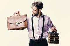 Άτομο ή δάσκαλος με τη σκληρή τρίχα, τα γυαλιά και το περίεργο πρόσωπο Nerd ή βιβλιόψειρα που φορά suspenders Άτομο με το χαρτοφύ στοκ εικόνα