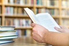 Άτομο ή σπουδαστής που διαβάζει ένα βιβλίο δημόσια ή τη σχολική βιβλιοθήκη στοκ εικόνες με δικαίωμα ελεύθερης χρήσης