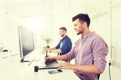 Άτομο ή σχεδιαστής με τον υπολογιστή και ταμπλέτα στο γραφείο στοκ εικόνα