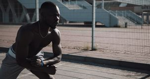 Άτομο αθλητών αφροαμερικάνων που κάνει τις δευτερεύουσες κοντόχοντρες επιθέσεις κοντά στο σύγχρονο στάδιο Κίνητρο αθλητικής worko απόθεμα βίντεο