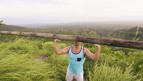 Άτομο αθλητών που ανυψώνει το βαρύ ξύλινο φραγμό στον τροπικούς λόφο και το τοπίο ορεινών περιοχών Άσκηση Τύπου κατάρτισης Bodybu απόθεμα βίντεο