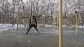Άτομο αθλητών που κάνει την άσκηση ικανότητας κατά τη διάρκεια της υπαίθριας κατάρτισης στη χειμερινή ημέρα φιλμ μικρού μήκους