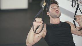 Άτομο αθλητών που χρησιμοποιεί τους βρόχους ικανότητας για την άσκηση τραβήγματος UPS στη γυμναστική φιλμ μικρού μήκους