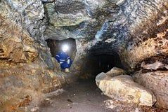 Άτομο ανθρακωρύχων υπόγεια σε μια σήραγγα ορυχείων Εργαζόμενος στις φόρμες, κράνος ασφάλειας Στοκ Φωτογραφία