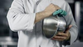 Άτομο αρχιμαγείρων που προετοιμάζεται να μαγειρεψει Το άτομο κινηματογραφήσεων σε πρώτο πλάνο δίνει το γυαλίζοντας κύπελλο στην κ απόθεμα βίντεο