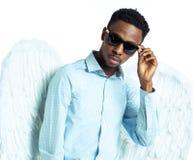 Άτομο αφροαμερικάνων με τα φτερά αγγέλου στα γυαλιά ηλίου Στοκ Φωτογραφία