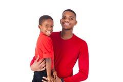 Άτομο αφροαμερικάνων με το κράτημα του μικρού παιδιού του απομονωμένου στο wh Στοκ Φωτογραφίες