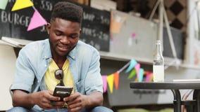 Άτομο αφροαμερικάνων με το smartphone στο φορτηγό τροφίμων απόθεμα βίντεο