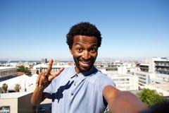 Άτομο αφροαμερικάνων που υπερασπίζεται το αστικό υπόβαθρο με το σημάδι ειρήνης Στοκ Φωτογραφίες
