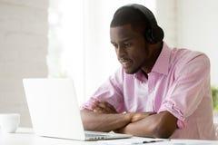 Άτομο αφροαμερικάνων που φορά τα ακουστικά που χρησιμοποιούν το lap-top που εξετάζει στοκ φωτογραφία