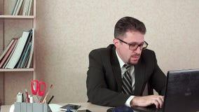 Άτομο διευθυντών γραφείων με τη γενειάδα και τα γυαλιά Εργασίες για ένα lap-top απόθεμα βίντεο
