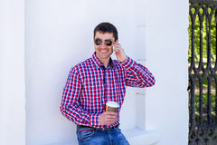 Άτομο ενάντια σε έναν τοίχο, με τον καφέ που μιλά στο τηλέφωνο, το καλοκαίρι με τα γυαλιά και το πουκάμισο, ευτυχής χαμογελώντας  Στοκ Εικόνα